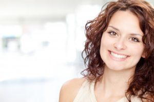 woman brunette smiling happily perfect teeth