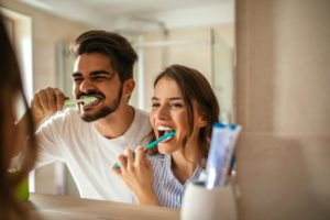 People smiling while brushing teeth